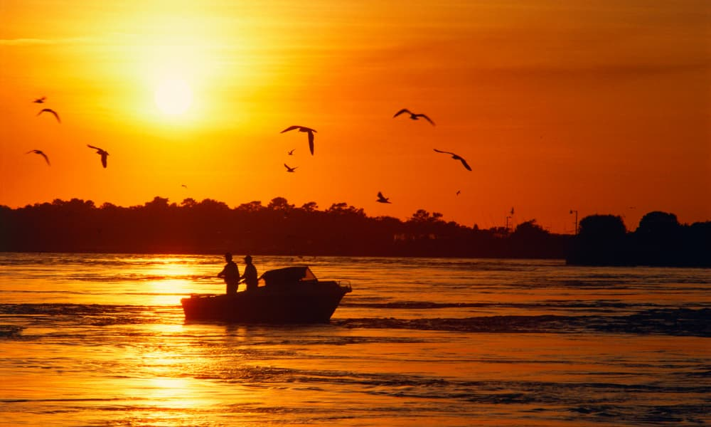 two people fishing at sunset from a boat