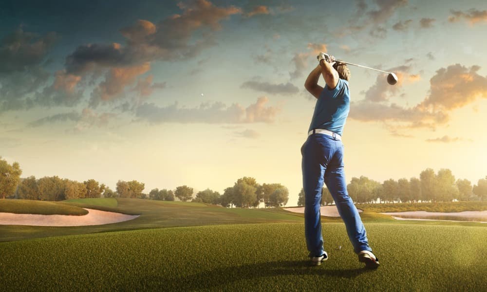A golfer swings a club on a beautiful Rehoboth Beach golf course