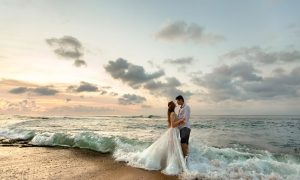 A couple embraces as waves wash over their feet during a Rehoboth Beach wedding.